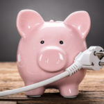 Pink ceramic piggybank with electrical plug, symbolizing how to save on energy.