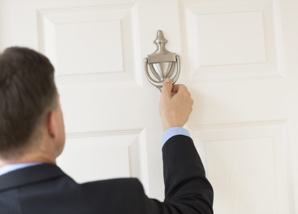 Salesperson in blue shirt and suit lifting a silver door knocker on a white door.