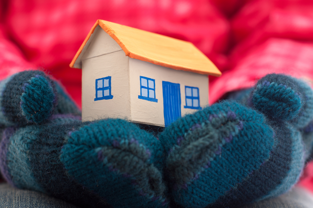 Small toy brown house with blue door and windows cradled by a person wearing a pink winter coat and thick blue striped mittens, representing keeping your house warm.
