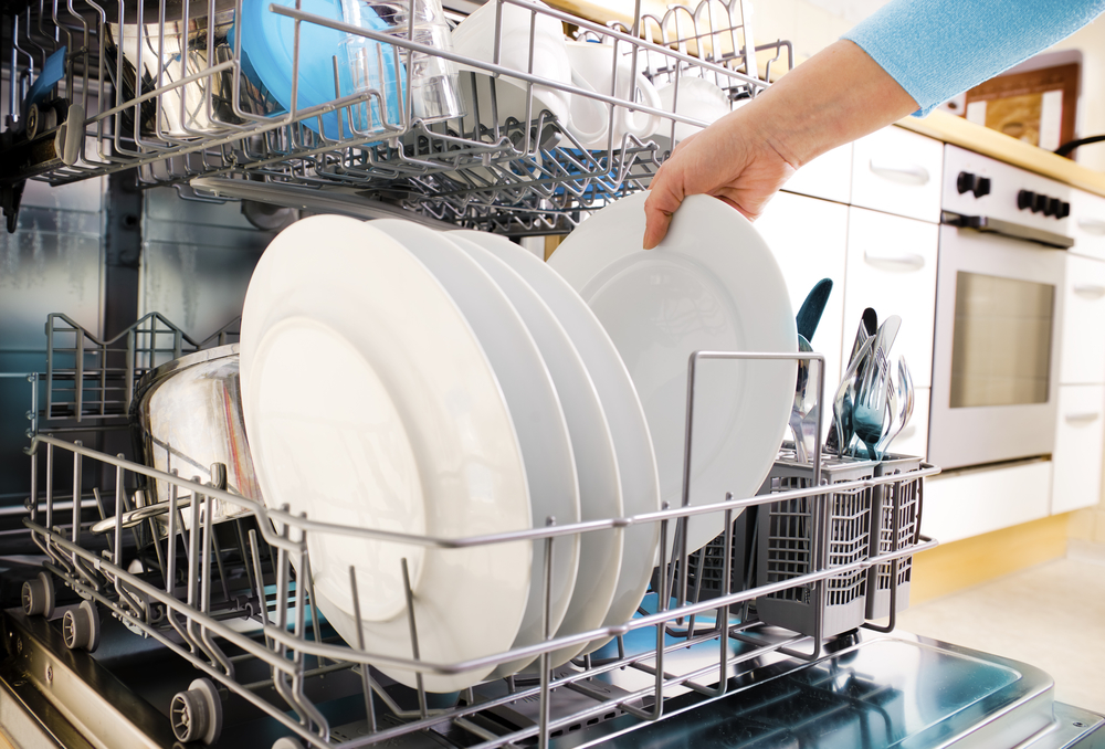 Woman taking a clean dinner plate from a dishwasher. Opening the dishwasher immediately following the clean cycle to let the dishes sir dry will help lower your electric bills.