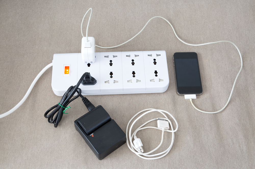 Smartphone and an electronic device plugged into an electric charging strip and consuming phantom energy.