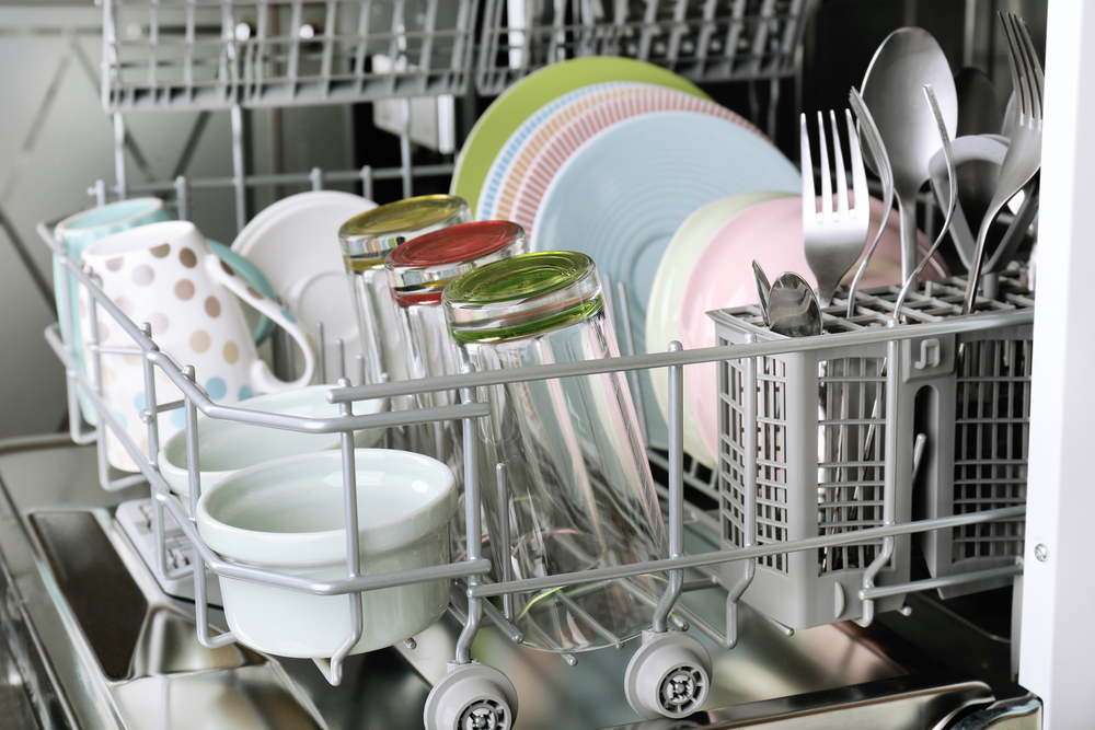 Open dishwasher filled with clean cups, glasses, plates and flatware. Only running a full dishwasher is one strategy to save energy while washing dishes.