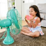 Young child with watermelon staying cool in front of a home fan. Circulating the air throughout your home is one way to save energy while keeping your house cool during the summer.